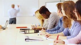 Leraar die in universiteitsklasse op whiteboard schrijven stock videobeelden