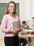 Leraar die zich met notitieboekje in klaslokaal bevindt Royalty-vrije Stock Foto