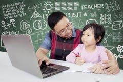 Leraar die zijn student helpen die laptop met behulp van Royalty-vrije Stock Afbeeldingen