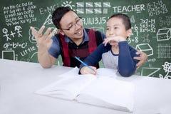 Leraar die zijn student helpen te tellen Royalty-vrije Stock Fotografie