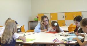 Leraar en een schoolmeisje die bij de creatieve les schilderen Hoog - kwaliteits4k lengte stock footage
