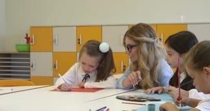 Leraar en een schoolmeisje die bij de creatieve les schilderen Hoog - kwaliteits4k lengte stock video