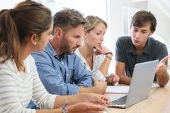 Leraar en groep studenten die aan latop werken Stock Fotografie