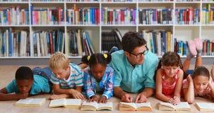 Leraar en jonge geitjes die op het boek van de vloerlezing in bibliotheek liggen stock video