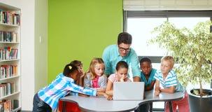 Leraar en jonge geitjes gebruikend laptop in klaslokaal stock video