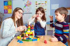 Leraar en jonge geitjes samen met kleurrijke de bouwstuk speelgoed blokken stock fotografie