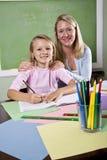 Leraar en jonge student in klasse het schrijven stock foto