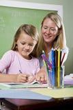 Leraar en jonge student in klasse het schrijven royalty-vrije stock afbeelding