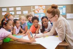 Leraar en leerlingen die bij bureau samenwerken Royalty-vrije Stock Afbeelding