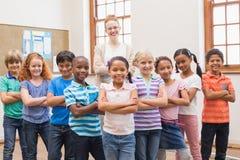 Leraar en leerlingen die bij camera in klaslokaal glimlachen Royalty-vrije Stock Foto