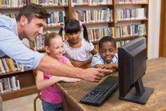 Leraar en leerlingen die computer met behulp van bij bibliotheek royalty-vrije stock afbeelding