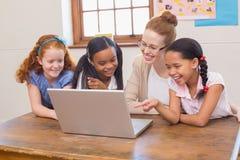 Leraar en leerlingen die laptop bekijken Royalty-vrije Stock Foto
