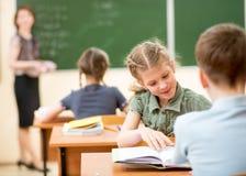 Leraar en schooljonge geitjes in klaslokaal bij les Stock Foto