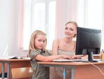 Leraar en schoolmeisje bij de computer Royalty-vrije Stock Afbeeldingen