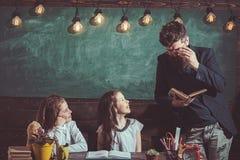 Leraar en schoolmeisjes op klaslokaalachtergrond Huis het scholen en terug naar schoolconcept Jonge geitjes en privé-leraar met h royalty-vrije stock afbeeldingen