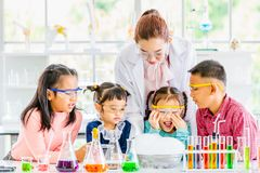 Leraar en studenten in laboratorium, rookvlotter uit stock afbeeldingen
