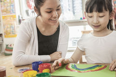 Leraar en studentenvinger het schilderen in kunstklasse Stock Foto's