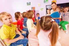 Leraar gelezen boek aan kleine jongens en meisjes Royalty-vrije Stock Afbeeldingen