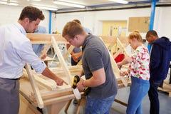 Leraar Helping College Students die Timmerwerk bestuderen royalty-vrije stock afbeelding