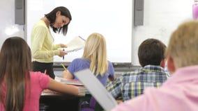 Leraar Helping Female Pupil in Klasse stock footage