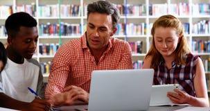 Leraar het bijwonen schoolkinderen in hun studies 4k stock videobeelden
