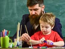 Leraar met baard, vader en weinig zoon in klaslokaal terwijl het trekken, het creëren, bord op achtergrond Talent en stock foto's