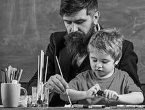 Leraar met baard, vader en weinig zoon in klaslokaal terwijl het trekken, het creëren, bord op achtergrond Talent en royalty-vrije stock afbeeldingen