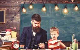 Leraar met baard, vader en weinig zoon in klaslokaal terwijl het trekken, het cre?ren, bord op achtergrond Kunstenles stock afbeeldingen