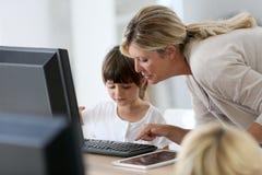 Leraar met kinderen op school die computer met behulp van royalty-vrije stock afbeelding