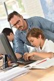 Leraar met studenten in de gegevensverwerking van klasse stock foto