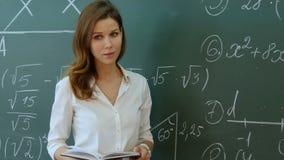 Leraar Standing In Front Of Class Asking Question en het glimlachen stock footage