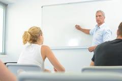 Leraar vooraan witte raad in klaslokaal Stock Fotografie
