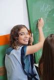 Leraar Writing On Chalkboard in Klaslokaal royalty-vrije stock foto's
