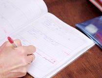 Leraarsgeschrift in schoolagenda Stock Foto's