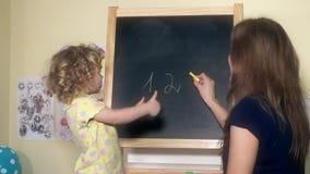 Leraarsvrouw het schrijven aantallen op krijt zwarte raad voor weinig kindmeisje stock video