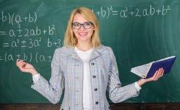 Leraarsvrouw met de achtergrond van het boekbord Waarom de leraar van zieken met spanning ophield met Overwerken en gebrek aan st stock foto