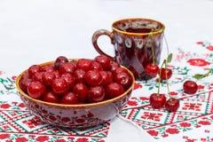Lerabunke och kopp med körsbäret Arkivfoto