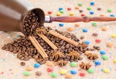Lerakruset fyllde med kaffebönor, anis och kanelbruna pinnar med färgrika godisar royaltyfria foton
