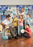 Leraren die Gitaar met Leerlingen spelen stock afbeelding