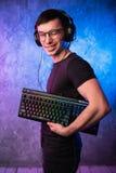 Lerdo do computador com o teclado sobre o rosa colorido e a parede leve de néon azul imagens de stock royalty free