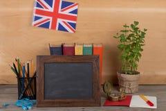 Lerend engelstalig concept - leeg bord, vlag van het Verenigd Koninkrijk, boeken, potloden, kompas stock foto