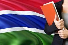 Lerend Gambiaans taalconcept Jonge vrouw die zich met de vlag van Gambia op de achtergrond bevinden De boeken van de leraarsholdi royalty-vrije stock afbeeldingen