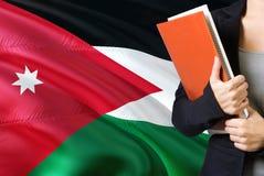 Lerend Jordanian taalconcept Jonge vrouw die zich met de vlag van Jordanië op de achtergrond bevinden De boeken van de leraarshol royalty-vrije stock afbeeldingen