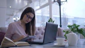 Lerend op Internet, las de vrouwelijke student boek en schrijft nota's in notitieboekjezitting bij lijst met laptop stock footage