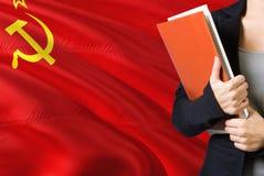 Lerend Russisch taalconcept Jonge vrouw die zich met de vlag van Sovjetunie op de achtergrond bevinden De boeken van de leraarsho stock fotografie