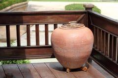 Lergodskrus som lokaliseras på hörnet av terrassen av huset Arkivbild