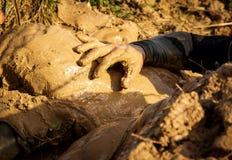 Lerig hinderlopplöpare i handling Gyttjakörning Detaljer av händerna fotografering för bildbyråer