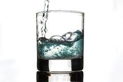Lerigt vatten i ett exponeringsglas på en vit bakgrund arkivfoton