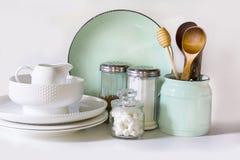 Lerkärl, bordsservis, redskap och annat olikt vit och turkosmaterial på vit bordsskiva arkivbild