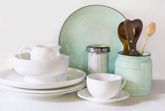 Lerkärl, bordsservis, redskap och annat olikt vit och turkosmaterial på vit bordsskiva Kökstilleben som bakgrund f fotografering för bildbyråer